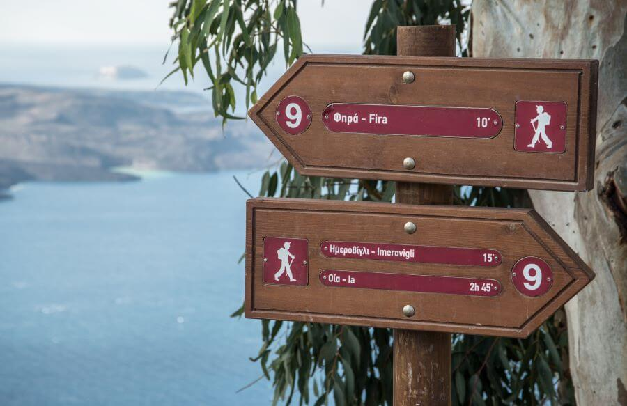Signpost on Santorini caldera cliff-top hike from fira to oia