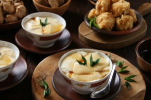 bean curd in warm soybean (tofu) pudding, served together with other street food snack of fried tofu.